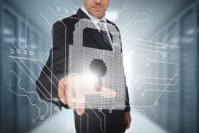 Businessman selecting a futuristic padlock with a data center on