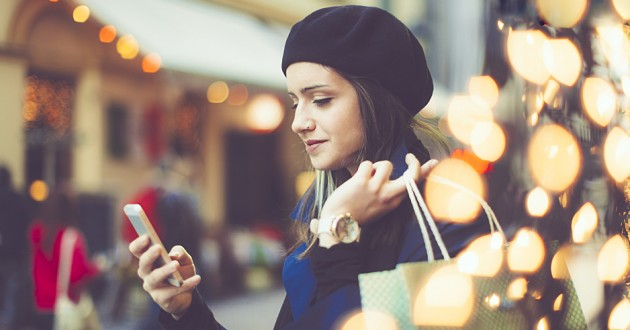 A mobile user browses a retail app while shopping for the holidays.