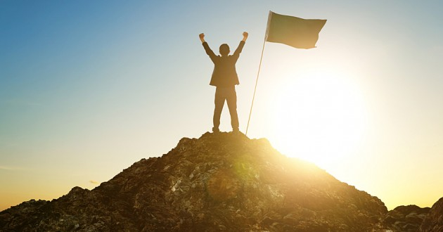 A man raising his hands victoriously with a flag planted at the top of a hill.
