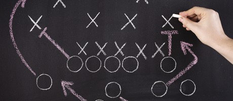 A hand drawing football plays on a chalkboard.