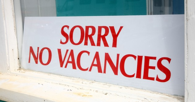 A ' Sorry No Vacancies' sign in a motel window.