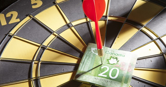 A Canadian bank note pinned to a bull's-eye by a dart.