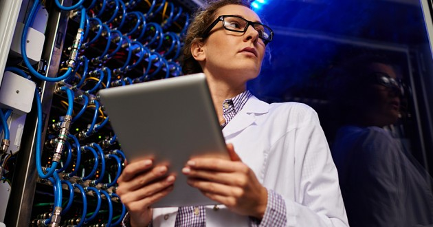An IT technician tends to network servers.