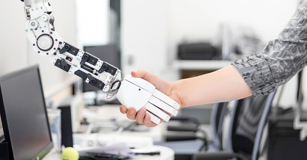 A human shaking hands with a robot.
