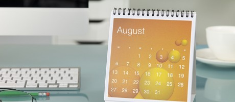 An August calendar on an office desktop.