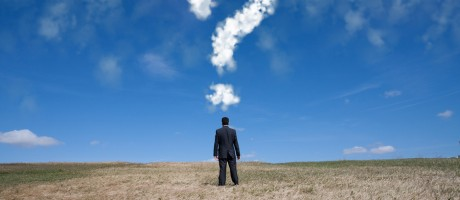 A businessman standing in a field beneath a cloud in the shape of a question mark.