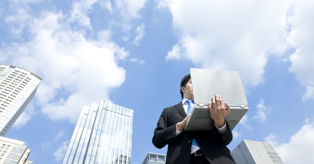 A man with a laptop in front of office buildings and clouds.