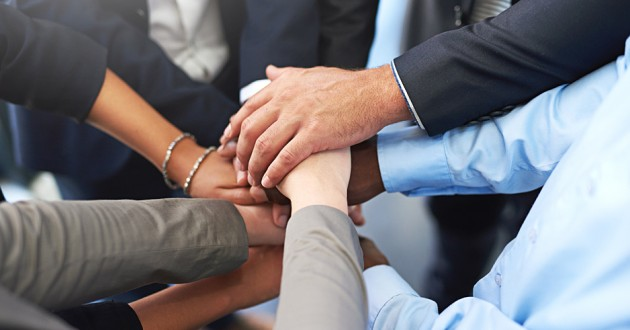 A group of businesspeople joining hands.