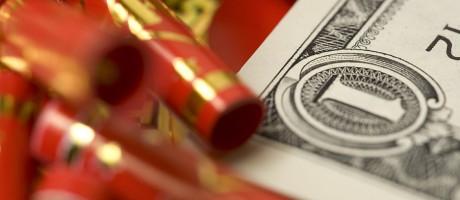 Firecrackers lying on top of a U.S. dollar bill.