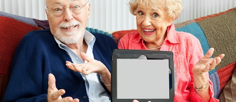 An older couple clueless about how to use a tablet.