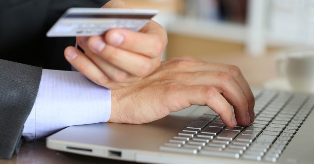 A businessman using a payment card on a computer.