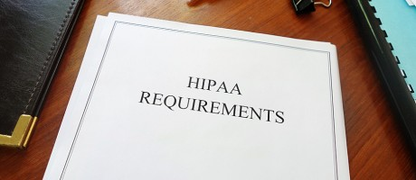 A packet of HIPAA requirements on a desk.