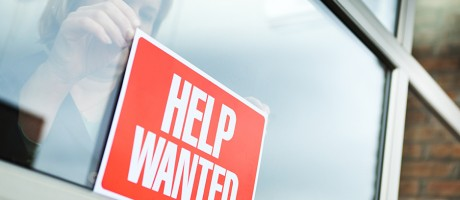 A woman hanging a help wanted sign in a window.