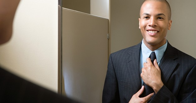 A business professional fixing his tie in front of a bathroom mirror.