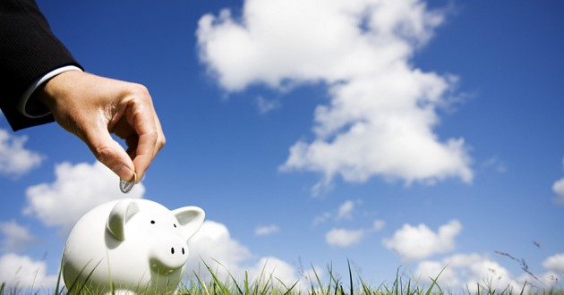 A businessman placing a coin into a piggy bank against a backdrop of clouds.