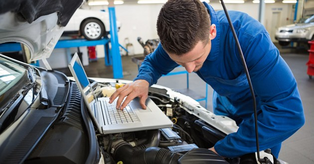 An auto mechanic using a laptop to diagnose a problem under the hood of a car.