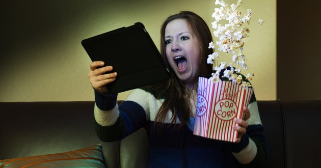 A woman eating popcorn while using a smart tablet.