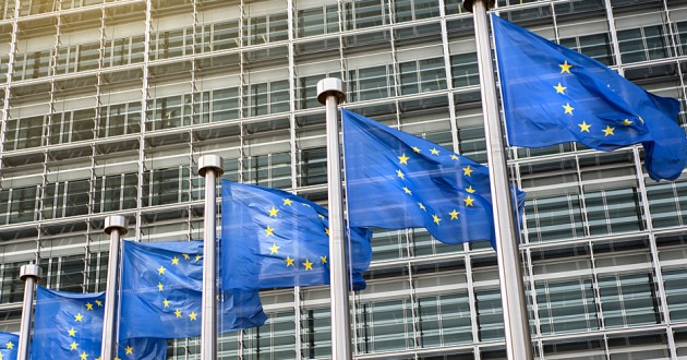 European Union flags flying in front of an official building.