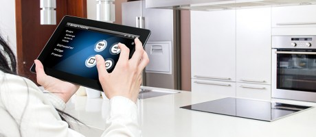 A woman using a tablet to control internet-connected appliances.