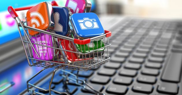 A miniature shopping cart filled with app icons on a computer keyboard.