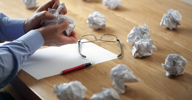 A worker tearing up paper surrounded by wads of scrap paper.