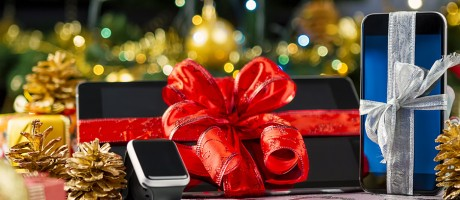 A smartphone, smart tablet and smartwatch under a Christmas tree.