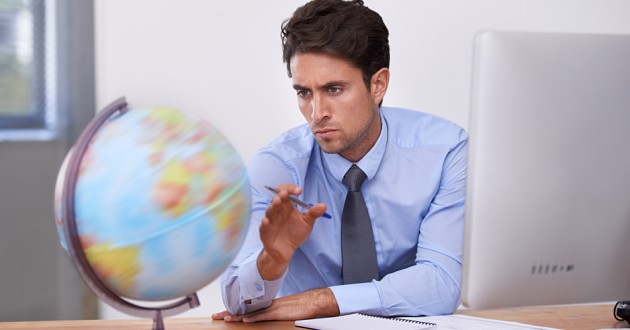 A businessman spinning a globe on his desktop.