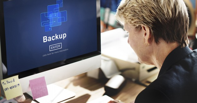 A businesswoman backing up files on a computer.