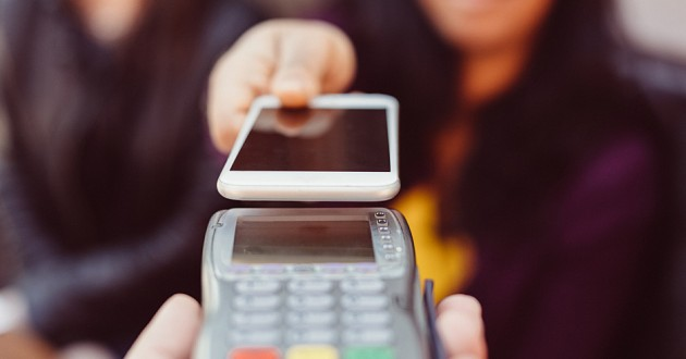 A woman conducting a financial transaction using her smartphone.
