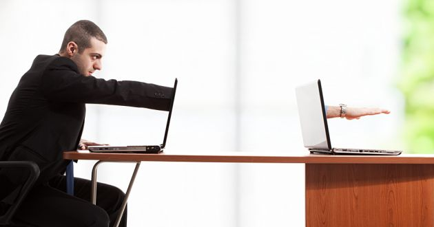 A businessman reaching into one computer monitor and out from another.