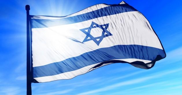 An Israel flag flying against a blue sky.
