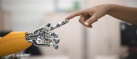 A human touching the fingertip of an artificially intelligent machine.