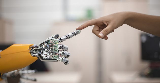 A human touching the fingertip of an artificially intelligent machine.