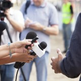 A business leader conducting an interview with the press.