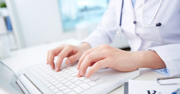 A health care professional entering data into a computer.