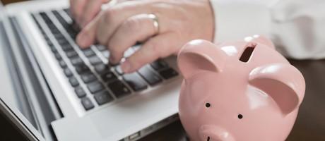 A man using a laptop beside a piggy bank.