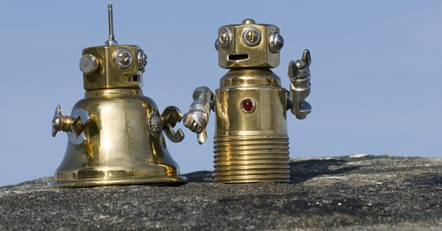 Two miniature robot figured on a rock surface.