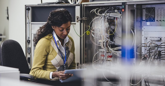 An IT professional reviewing network data on a smart tablet in a server room.