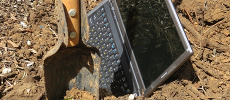A laptop being buried in a hole.