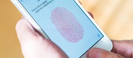 A smartphone user logging in with a fingerprint scanner.