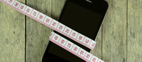 A smartphone wrapped in measuring tape.