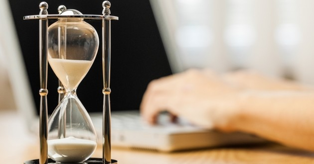 An hourglass beside a person typing on a laptop.
