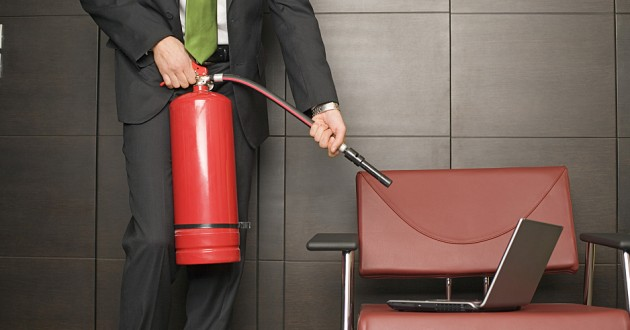 A businessman pointing a fire extinguisher at a laptop computer.