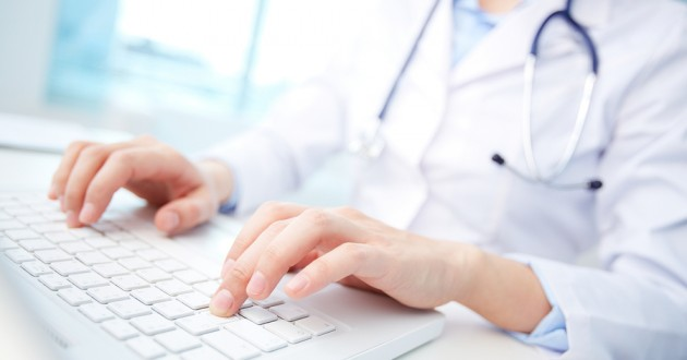 A medical employee typing on a computer.