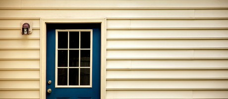 A blue door against the tan siding of a house.