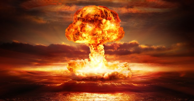 A mushroom cloud rising over a body of water.