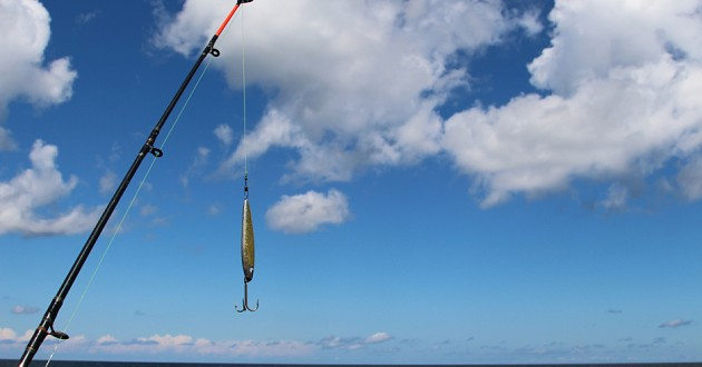 A fish hook hanging from a fishing rod against a backdrop of clouds.