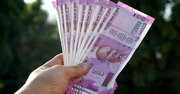 A hand holding Indian paper currency.