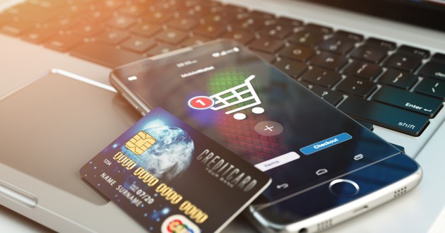 A credit card and a phone open to an online shopping cart sitting on top of a keyboard.