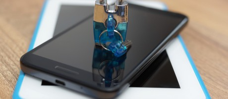 A padlock on top of a phone and tablet.